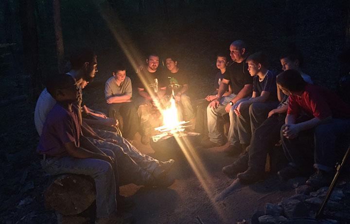 Boys around campfire