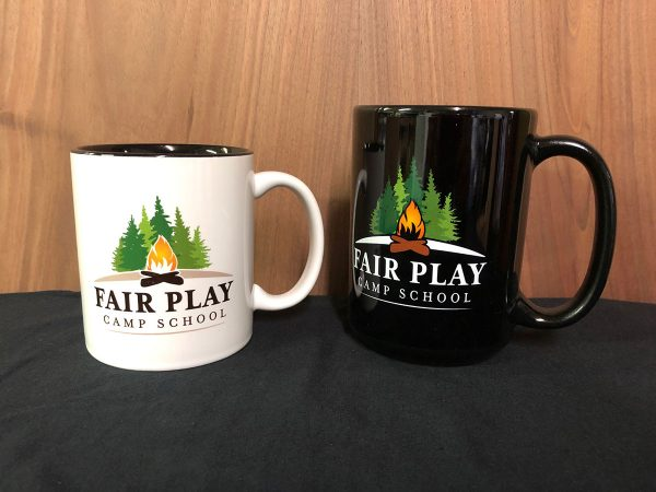 white and black coffee mugs from Fair Play Camp School