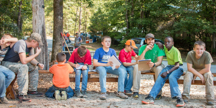 Guy at boys camp with fellow campers