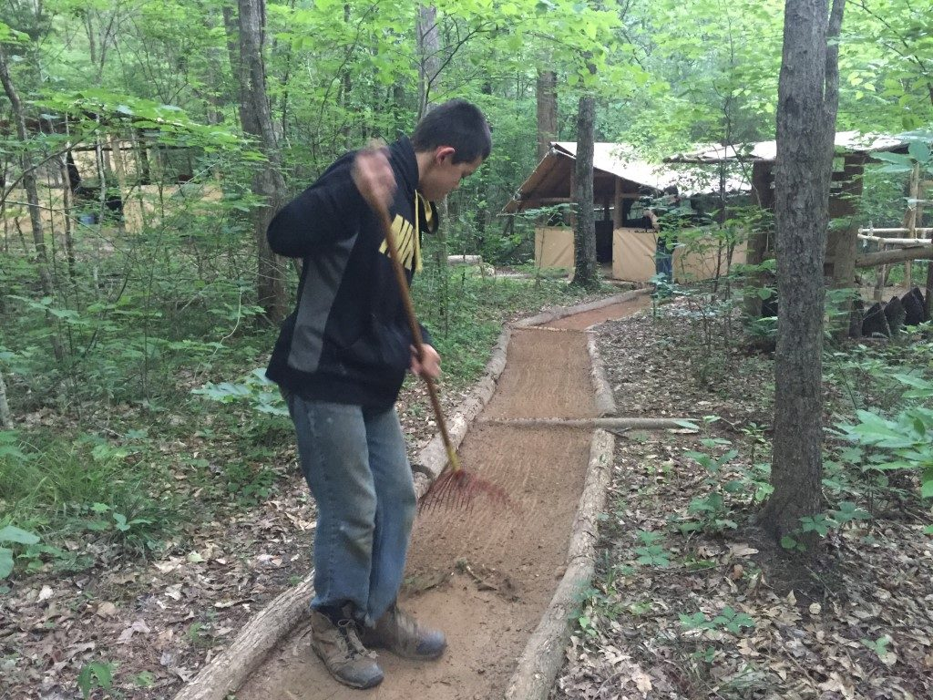 young man sweeping a trail, learning personal responsibility